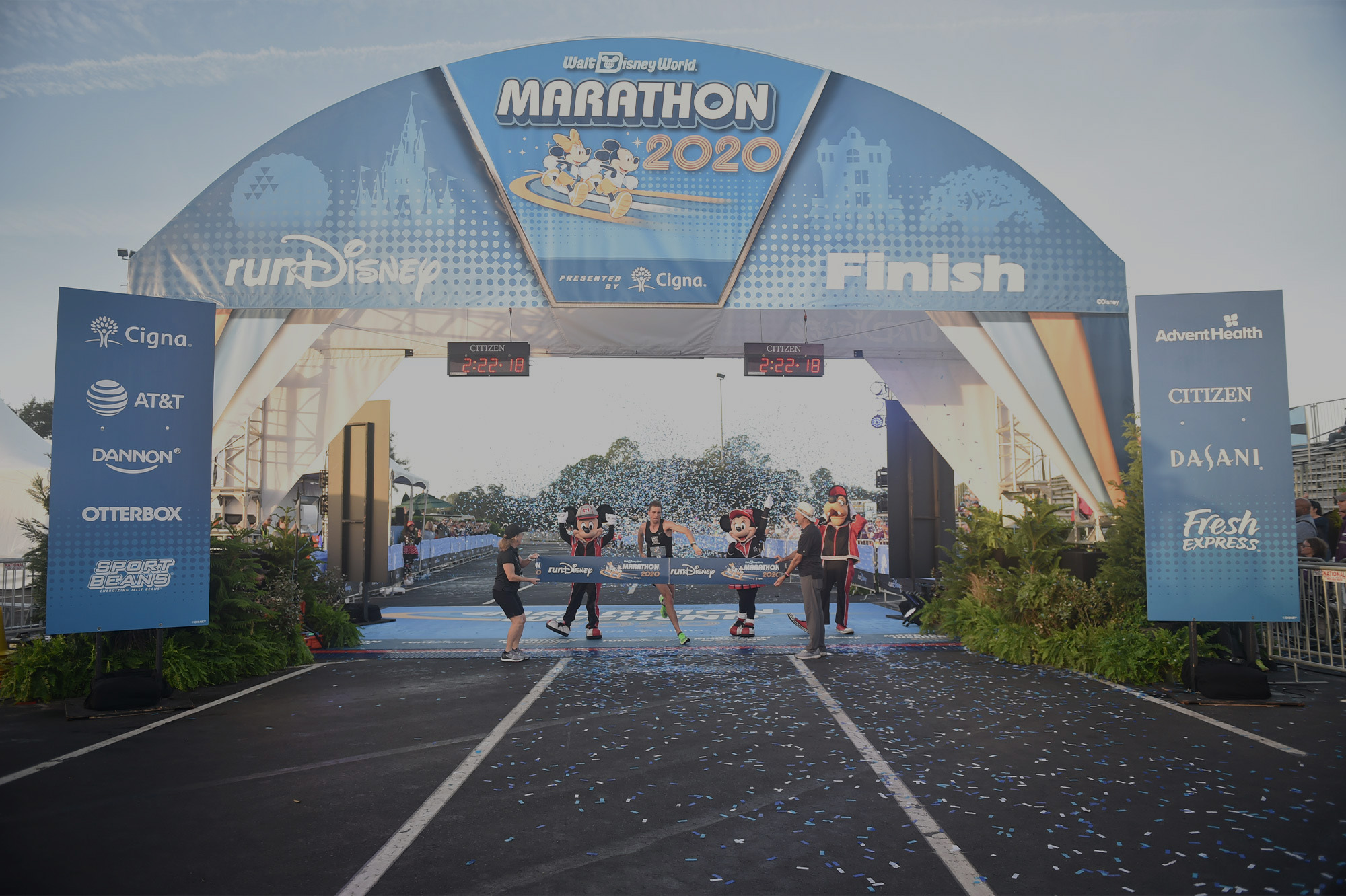Runner crossing runDisney marathon finish line.